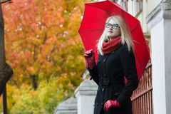 Blonde student girl with red fully collapsible umbrella and thumb in pocket posing at autumn street background Royalty Free Stock Photo