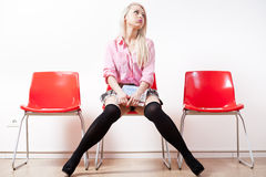 Blonde student girl in a waiting room bored Stock Photography