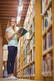 Blonde student reading book next to bookshelf Royalty Free Stock Image