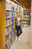 Blonde student reading book next to bookshelf Royalty Free Stock Photography