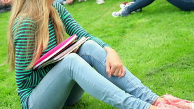 Blonde student smiling at camera with friends behind her on grass stock video footage