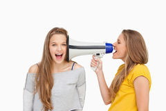 Blonde student using a loudspeaker on her friend Stock Photo