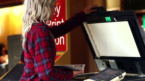 Blonde student using the photocopier in the library stock footage