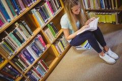 Blonde Studentenlesung beim Sitzen auf Büchern Lizenzfreies Stockbild