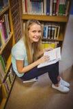 Blonde Studentenlesung beim Sitzen auf Büchern Stockfoto