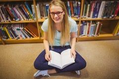 Blonde Studentenlesung beim Sitzen auf Büchern Stockbilder