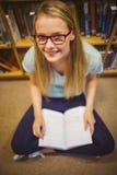 Blonde Studentenlesung beim Sitzen auf Büchern Stockfotografie
