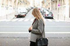 Blonde Studentin, die auf Straße nahe Autos in der Stadt geht Stockbilder