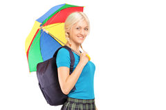 Blonde Studentin, die mit Regenschirm geht und Kamera betrachtet Stockfotos
