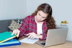 Blonde Studentin, die am Schreibtisch lernt Stockfotografie
