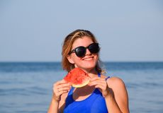 A blonde in sunglasses eats a watermelon by the sea. A juicy watermelon in the hands of a woman stock photography