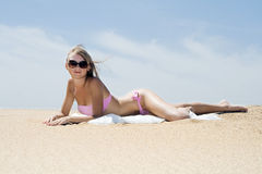 Blonde in sunglasses lies on warm sand Royalty Free Stock Photo
