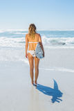 Blonde surfer in white bikini holding her board on the beach Stock Photography