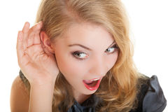 Blonde surprised gossip girl with hand behind ear listening secret Stock Photos