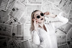 Blonde surrounded with newspapers Stock Image
