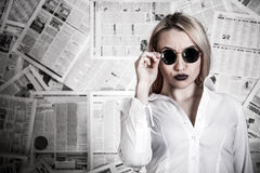 Blonde surrounded with newspapers Royalty Free Stock Images