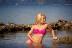 Blonde in swimsuit side-view half in sea Royalty Free Stock Image
