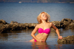Blonde in swimsuit side-view half in sea Royalty Free Stock Photos