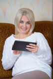 Blonde with a tablet PC Stock Images