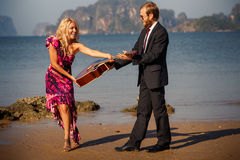 Blonde takes guitar from guitarist on beach Stock Photos