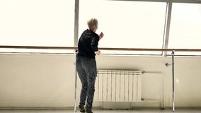 Blonde takes pictures of a beautiful Caucasian brunette in a white room stock video footage