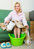 Blonde taking foot bath at home Stock Image