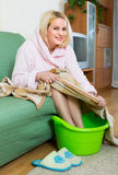 Blonde taking foot bath at home Royalty Free Stock Photography