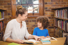 Blonde teacher and pupil reading books in the library. In school Royalty Free Stock Photography