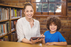 Blonde teacher and pupil using tablet in the library. Portrait of blonde teacher and pupil using tablet in the library in school Stock Images