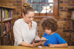 Blonde teacher and pupil using tablet in the library Stock Images
