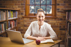 Blonde teacher reading book in the library Royalty Free Stock Photography