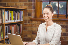 Blonde teacher using laptop in the library. Portrait of blonde teacher using laptop in the library in school Royalty Free Stock Image