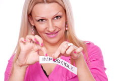 Blonde tearing the word impossible Stock Image