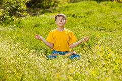 Blonde teen boy in a lotus position meditating, meditation on na Royalty Free Stock Photography