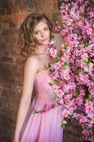 Blonde teen girl near a blossoming tree Royalty Free Stock Image