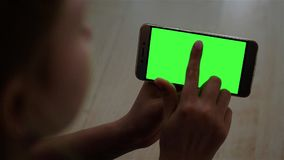 Blonde teenage girl holding a smartphone with green screen in landscape mode in daylight. stock video footage
