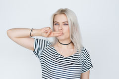 Blonde teenage girl posing. Beautiful blonde teenage girl posing, making a kissy face, standing against white wall. Two fingers gesture royalty free stock images