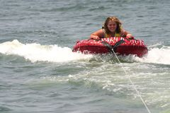 Blonde teenager being pulled on a inner tube raft Stock Photo