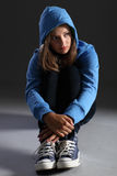 Blonde teenager girl alone and sad in blue hoodie. Hoodie on for distressed and frightened young blonde teenager girl sitting on floor looking scared and alone Royalty Free Stock Photography