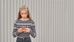 Blonde teenager girl dials the number and on the phone and talks. stock photography