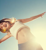 Blonde teenager girl jumping happy with the blue Stock Photo