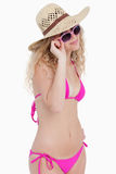 Blonde teenager looking over her sunglasses. Attractive blonde teenager looking over her sunglasses against a white background Royalty Free Stock Image