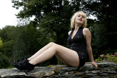 Blonde teenager modelling. Blonde teenager in retro 1950's playsuit modelling legs in country garden stock images