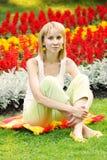 Blonde tegen bloemachtergrond Royalty-vrije Stock Foto's
