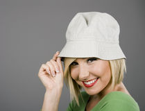 Blonde Tipping Cap and Smiling Royalty Free Stock Image