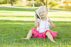 Blonde Toddler Girl Talking on Cell Phone Outdoors Stock Image