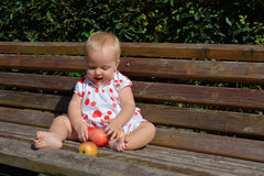 Blonde toddler laugh and sort apples Stock Photo