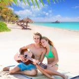 Blonde toeristenpaar het spelen gitaar bij strand Stock Foto
