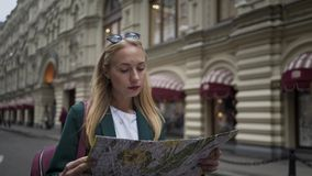 Blonde tourist looking at map walking Tverskaya street in Moscow, Russia summer. Attractive tourist with long blond hair looking at a map and wlaking along stock footage