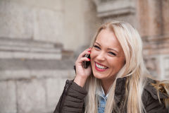 Blonde tourist phoning home from Europe Royalty Free Stock Photography